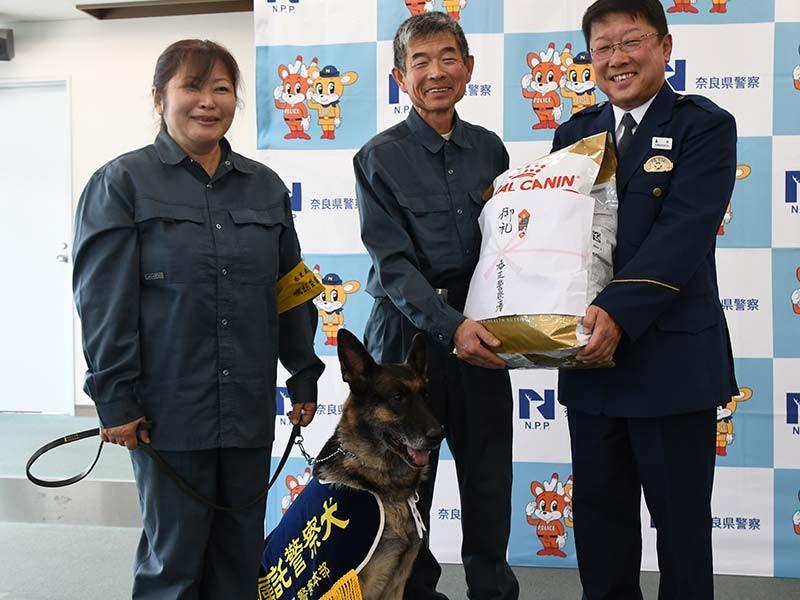 ドッグフードを受け取る今住千春さん(左)と博勝さん(中央)と警察犬のララ・オブ・スーパー・クリーク号